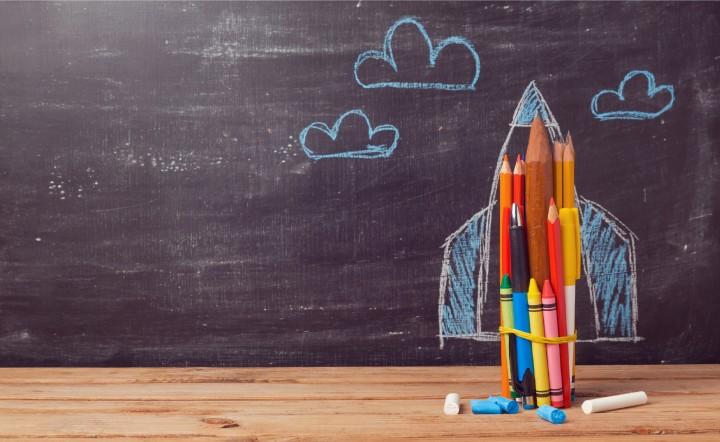 criatividade = conjunto de lapis de colorir amarrados, colocados contra um quadro de giz que forma a imagem de um foguete com nuvens. os lapis sao o corpo do foguete