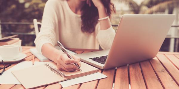 criatividade - mulher com notebook aberto escrevendo no caderno